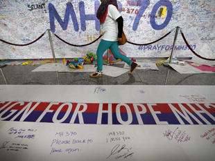 A woman walks past a banner filled with well-wishes for all involved with the missing Malaysia Airlines jetliner at the Kuala Lumpur International Airport. [ap/wide world photos]
